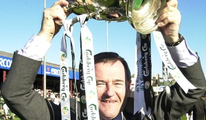 Des Denning lifts the FAI Cup following Dundalk's success in 2002